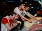 1963 group of men/teens playing pinball + driving game in arcade / educational