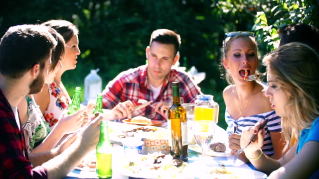 Group of mid 20's people having lunch outdoors.