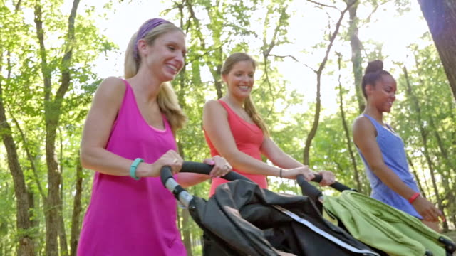 Gruppo di mamme esercitare insieme al parco, spingendo passeggini