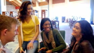 Group of multi-ethnic home school students talk and laugh with one another in a local public library