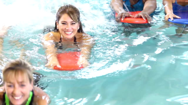 Group of multiracial  women swimming with kickboards