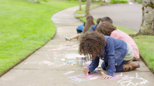 Group of neighborhood children playing together outside with sidewalk chalk