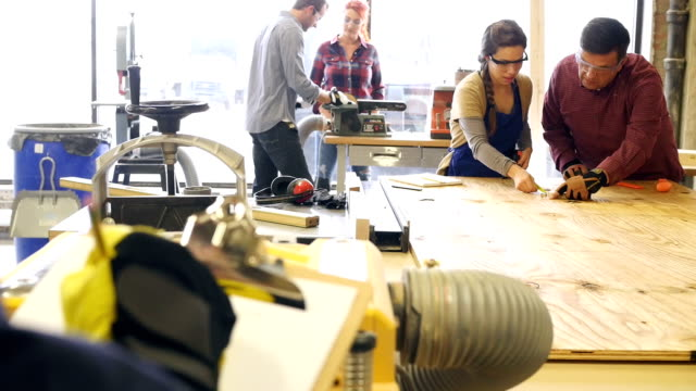 Group of people are working together on projects in community woodworking shop