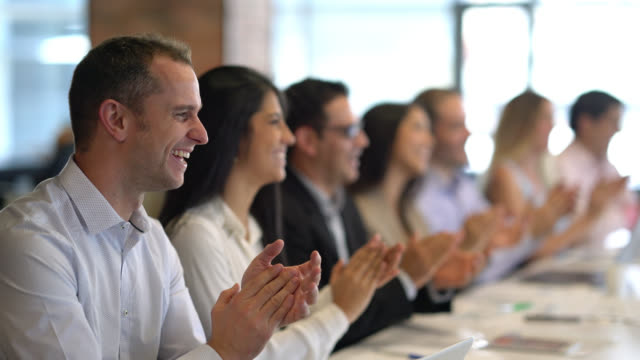 Group of people at a business meeting applauding someone