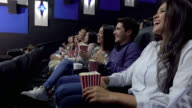 Group of people at the cinema watching a funny movie