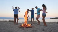 Group of people dancing by bonfire at the beach.