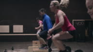 Group of people doing boxjumps in a gym box