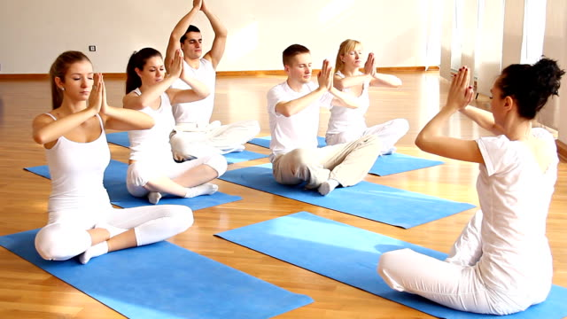 Group of people  doing yoga exercises with instructor.