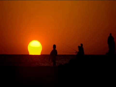 Group of people fishing against orange sunset on beach girl in silhouette runs past sun