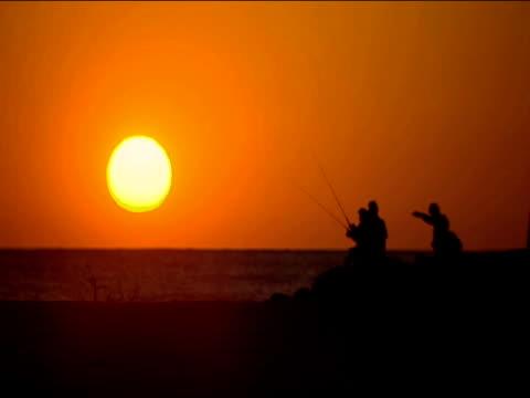 Group of people fishing against orange sunset on Florida beach
