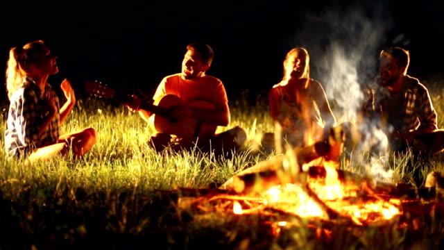 Groep mensen ontspannen door kampvuur.