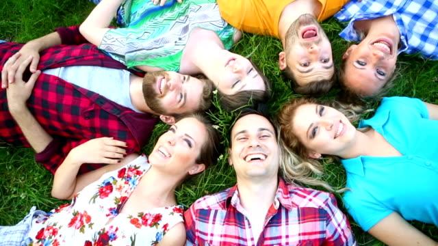 Groep mensen ontspannen in gras.