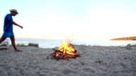 Group of people sitting by bonfire at the beach.