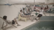 Group of people spending time together by the swimming pool at a surf camp