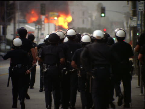 Group of policemen in riot helmets walking on street / burning building in background / Los Angeles riots