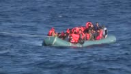 A group of refugees on their inflatable boat which is in danger of sinking are being rescued by the crews as the Turkish Coast Guard search and...