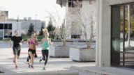 Group of runners running outside in urban city setting