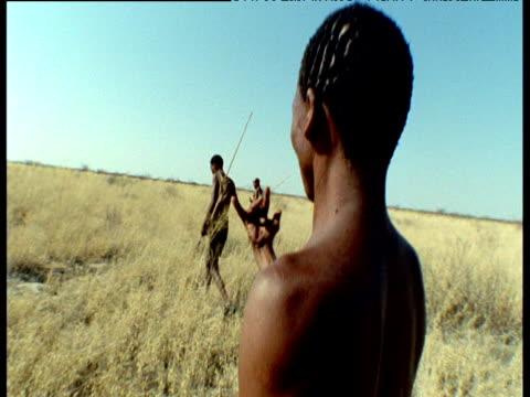 Group of San bushmen track Kudu antelope through Kalahari desert, Southern Africa