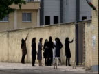 Group of scarved women painting wall, Iran (sound available)