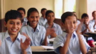 Group of school students clapping the classroom, Haryana, India