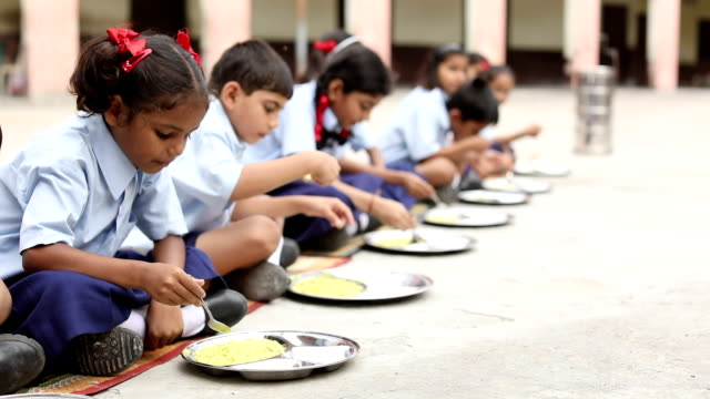Group of school students eating midday meal, Haryana, India