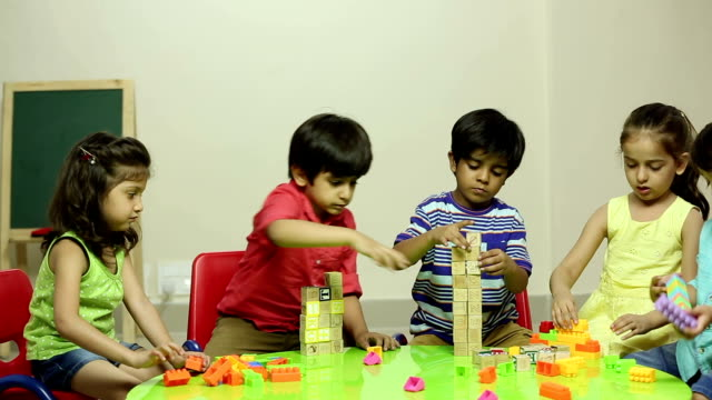 Group of school students making building blocks