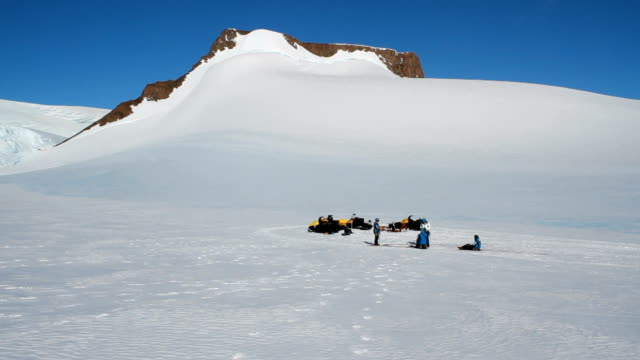 Group of scientists on flat snow in the mountains SANAE IV is the name of the South African Antarctic research base station It is located in...