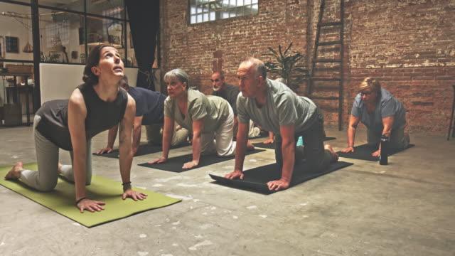 Grupp av seniorer träning i yogaklass