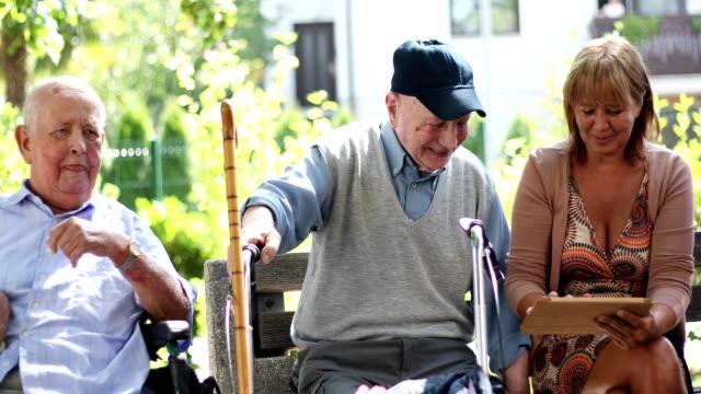 Group of Seniors Using Digital Tablet Outdoors