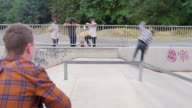 MS Group of skateboarders resting while watching friend ride in skate park