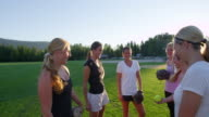 MS SLO MO Group of smiling female softball players tossing ball to each other after practice on field on summer evening