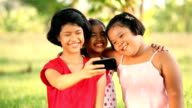 Group of smiling girls taking selfie with smartphone camera