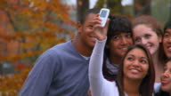 CU, PAN, Group of smiling teenagers photographing self with camera phone, Richmond, Virginia, USA