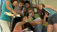 MS, Group of students photographing self with camera phone in college corridor, San Antonio, Texas, USA