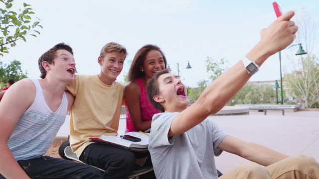 MS Group of teeanagers taking photo with their cell phone at skatepark / Santa Fe, New Mexico, United States