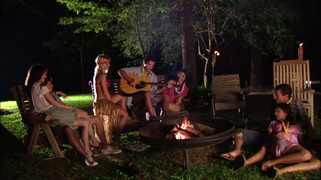 WS Group of teenage girls and young men roasting marshmallows around campfire, playing acoustic guitar and bongos / Mabank, Texas, USA
