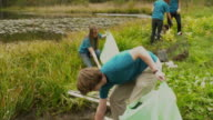 MS TU TD Group of teenagers cleaning lake shore from garbage, Dorset, Vermont, USA