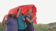 Group of teenagers playing with red blanket