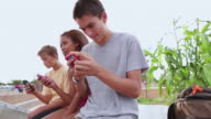 MS Group of teenagers texting or using their cell phones at skatepark / Santa Fe, New Mexico, United States
