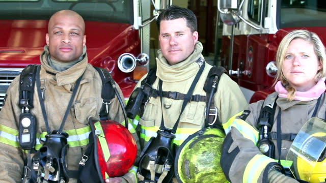 Group of three multi-ethnic firefighters at the station