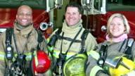 Grupp av tre multietniska brandmän vid stationen