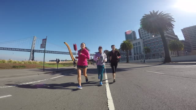 A group of three women running together in a urban area on a sunny day.