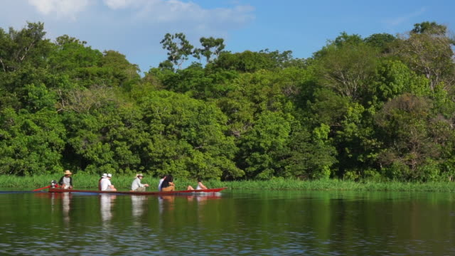 Group of tourist in a canoe in the Amazon rainforest and river