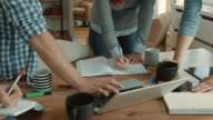 Group of unrecognizable freelancers using laptop and writing down a busines plan in the office.