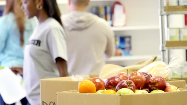 Group of volunteers organize food bank storage room