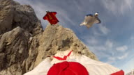 Group of wingsuit fliers descend mountain face