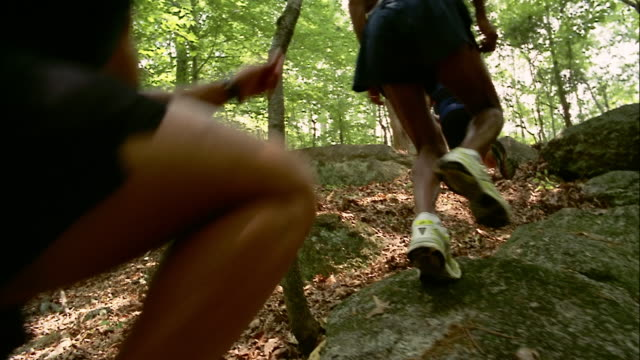 Group of women and men stepping over boulders while running up trail through woods / Red Top Mountain State Park, Georgia