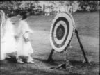 B/W 1916 group of women in dresses approach archery target + pull out arrows / Wellesley College, MA