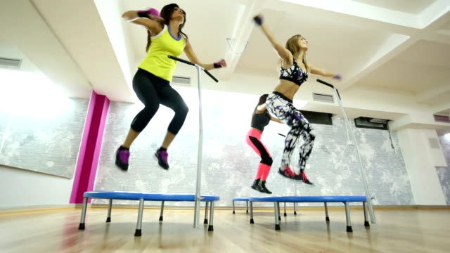 Group of women in the gym jumping on a mini trampoline