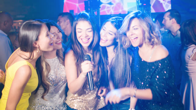 Group of women singing at a karaoke bar